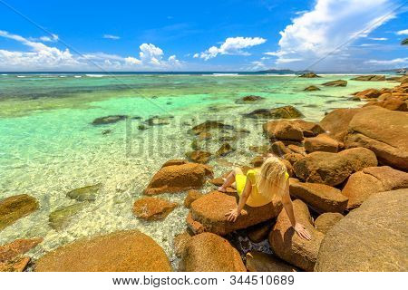 Blonde Tourist Woman In Yellow Sunbathing On A Rocks With Turquoise Indian Ocean At Seychelles. Anse