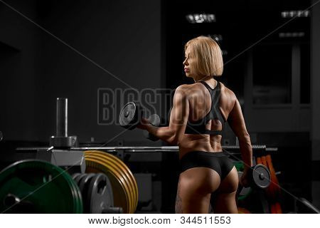 Back View Of Tattooed Blonde Female Bodybuilder Training Biceps With Dumbbells. Crop Of Fitnesswoman