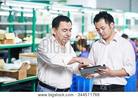 manager and chinese worker in factory, Managing and cooperation