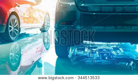 Closeup Chassis, Shaft, Muffler Of Car Reflected On Shiny Floor Of Showroom. New Luxury Car Parked I
