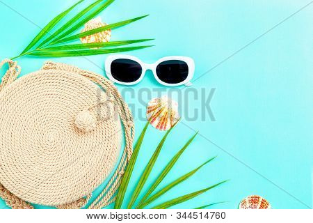 Travel. Feminine White  Sunglasses And Straw Handbag On Blue Background. Copy Space