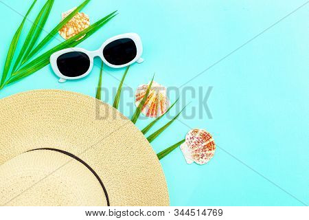 Travel Feminine Accessories. White  Sunglasses And Straw Hat On Blue Background. Copy Space