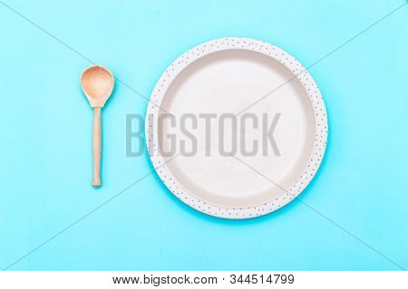Baby Bamboo Plate And Wooden Spoon Beige Color. Sustainable Lifestyle. Reusable