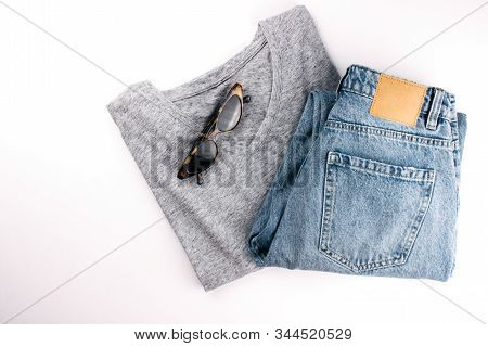 Gray Cotton T-shirt, Blue Jeans And Sunglasses Flat Lay On White Background. Clothes In Minimal Styl