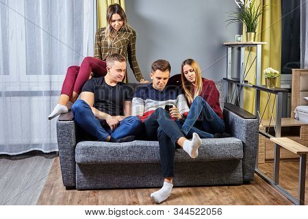 College Dorm Room With A Small Group Of Young People Relaxing On The Sofa. Young Men And Women Of St