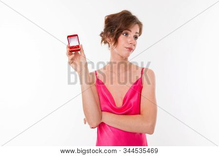 charming Caucasian girl in a pink dress with a neckline thinks whether to agree or not to a wedding proposal holding a box in her hand with a ring on a white background. poster