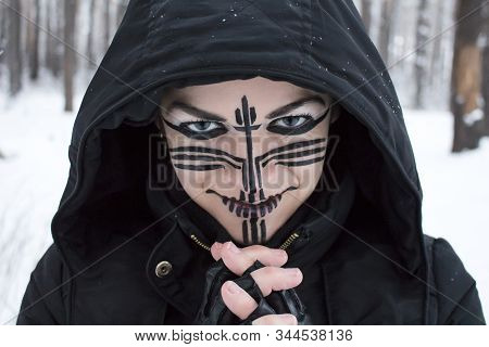 Portrait Of A Girl In A Black Hood With Fingers Crossed In Front Of Her In Leather Gloves With Makeu