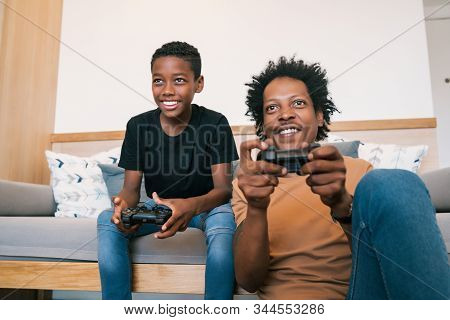 Portrait Of Happy African American Father And Son Sitting In Sofa Couch And Playing Console Video Ga