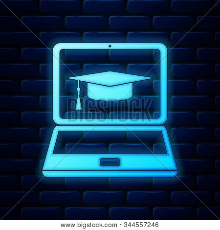 Glowing Neon Graduation Cap And Laptop Icon Isolated On Brick Wall Background. Online Learning Or E-