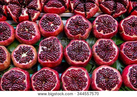 Many Pomegranate Cut In Half, Bright Colors. Tasty Juicy Fruit On Market.