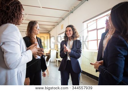 Confident Mature Employee Talking With Younger Colleagues. Cheerful Office Managers Talking In Offic
