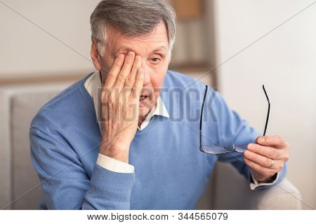 Glaucoma. Tired Elderly Man Massaging Eye Holding Eyeglasses Having Eyestrain And Ocular Tension Sit