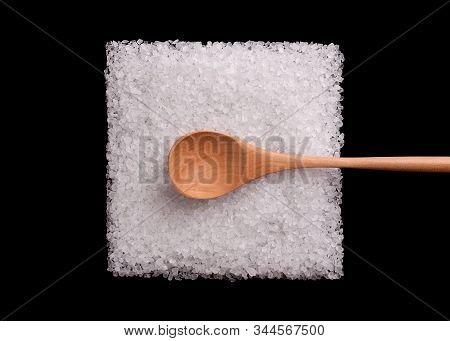 Salt Crystals On A Black Background. A Pile Of Salt In The Shape Of A Square With A Wooden Spoon. Sa