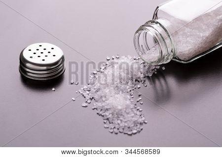 An Open Salt Shaker Lying On Its Side. Salt In The Kitchen. Sprinkled Salt.