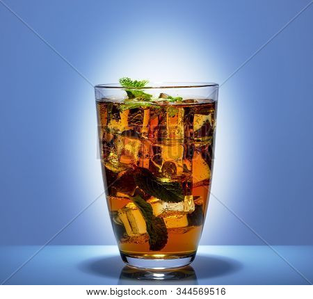 In A High Transparent Glass Glass A Soft Drink With Ice And Mint