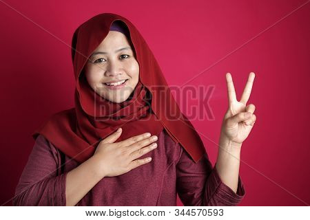 Portrait Of Happy Asian Muslim Woman Wearing Red Hijab Making Pledge Gesture, Hand On Chest Holding