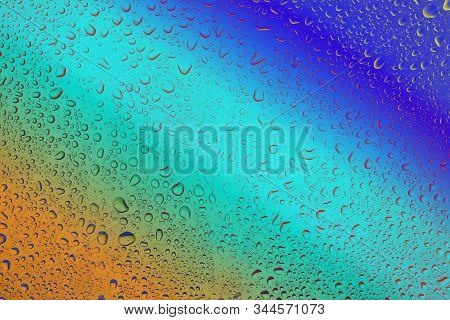 Water Bubbles On The Glass Close Up On A Beautiful Multicolored Background