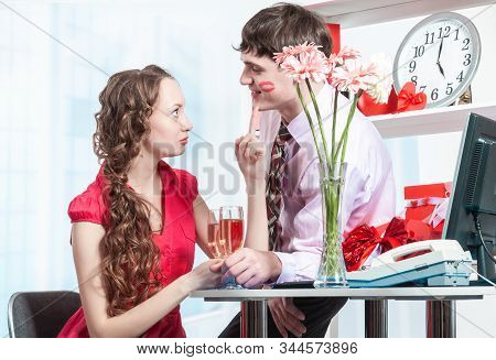 A Young Man, An Employee Of The Company Shows Courtship To His Colleague Young Woman With Curly Hair