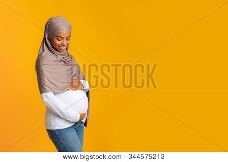 Happy Black Muslim Woman In Hijab Expecting Baby, Tenderly Touching Her Pregnant Belly While Posing