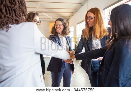 Group Of Confident Young Women Putting Hands Together In Circle. Beautiful Smiling Creative Team In