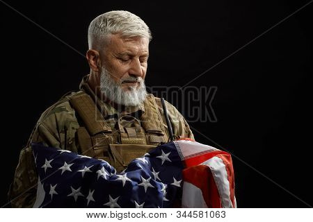 Front View Of Bearded American Military Veteran Holding Flag In Arms. Portrait Of Old Proud Male Off
