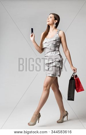 Woman Shopping Dress With Credit Card And Paper Bags, Fashion Model Full Length Studio Portrait, Gir