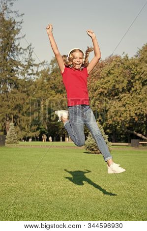 Energetic Song That Gets You Moving. Energetic Child Jumping Over Green Grass. Small Girl Enjoy Ener
