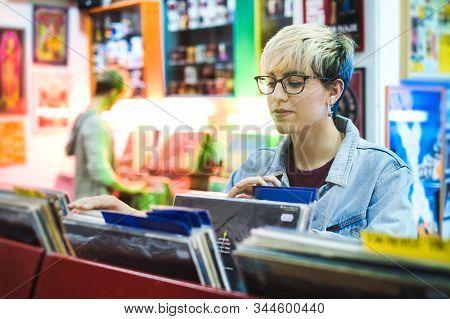 Young Woman Choosing Vintage Vinyl Lp In Records Shop