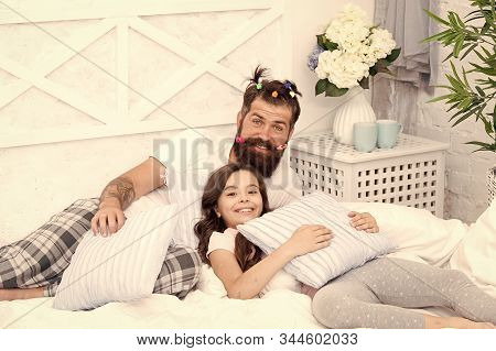 Father Bearded Man With Funny Hairstyle Ponytails And Daughter In Pajamas. Dad And Girl Relaxing In