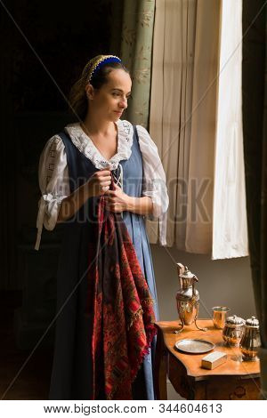 Pretty young woman in Renaissance costume looking through window of a property released authentic medieval castle in France