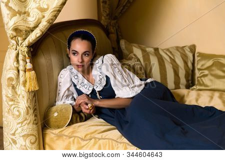 Dutch Master style portrait of a beautiful young woman in authentic renaissance costume lying on a luxury antique canopy bed in a golden bedroom of a medieval French castle with property release