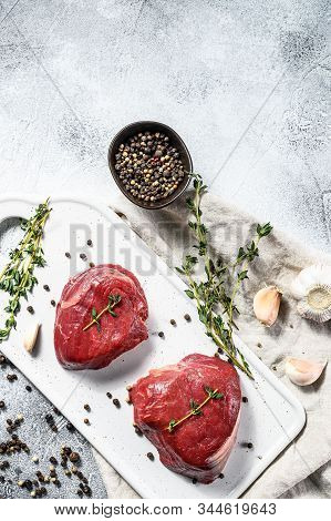 Raw Filet Mignon Steak On A White Chopping Board. Beef Tenderloin. Gray Background. Top View. Space