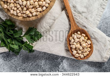 Dried Chickpeas In A Wooden Spoon. Healthy Vegetarian Food. Gray Background. Top View