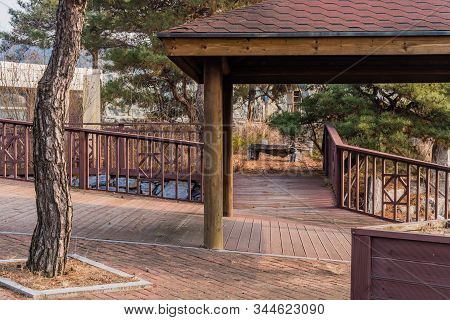 Wooden Covered Walkway And Railings In Neglected Public Park On Winter Day.
