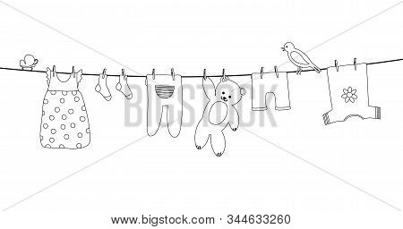 Baby Clothes On Clothesline. Kid Apparel After Washing Hanging On A Rope. Laundry For Newborn, Girl