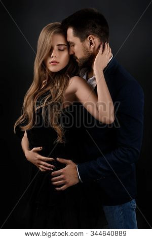 Elegant Couple On Black Background. Man Embracing Beautiful Woman In Black Dress