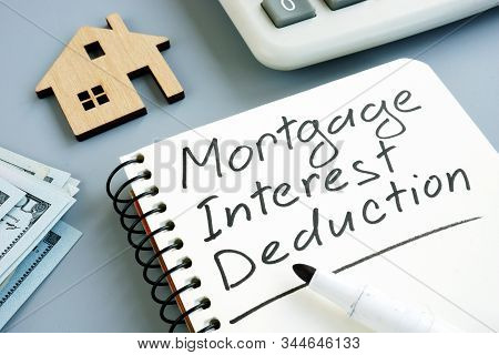 Mortgage Interest Deduction Concept. Model Of Home And Calculator.