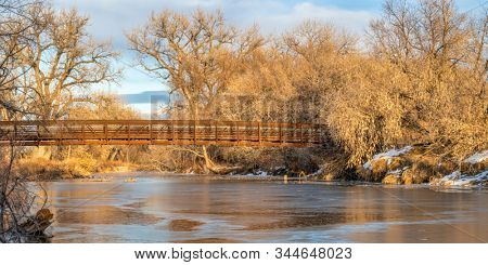 footbridge over frozen river - panorama of Poudre River Trail in northern Colorado in winter scenery, recreation and commuting concept