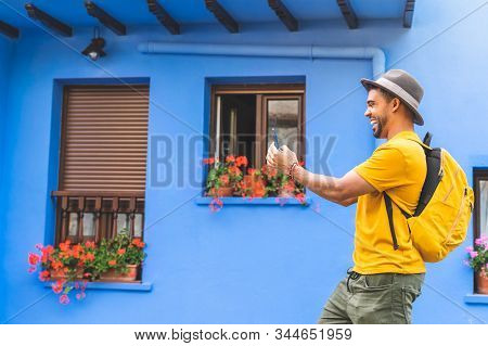 Young Latin Man Using Cellphone Smiling.