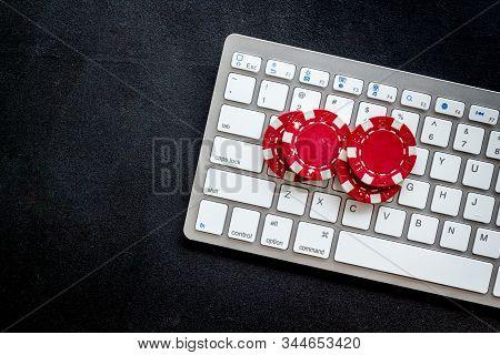 Online Poker. Chips Near Keyboard On Black Background Top-down Copy Space