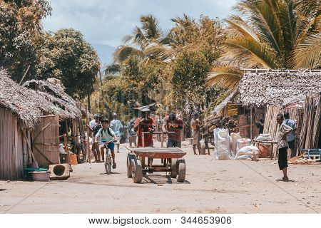 Madagascar October 18.2016: Two Malagasy Young Men Pushing A Wagon On Marketplace Street. Daily Life