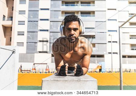 Latin American Man Training Outdoors Wearing Headphones.