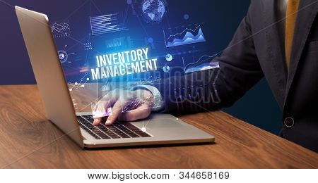 Businessman working on laptop with INVENTORY MANAGEMENT inscription, new business concept