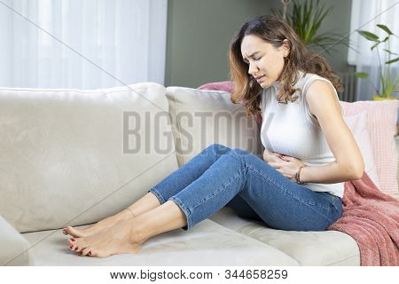 Sad Young Woman Sitting On The Couch And Feeling Spasm And Symptoms Of Pms