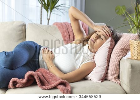 Young Woman Suffering From Stomachache On Sofa At Home