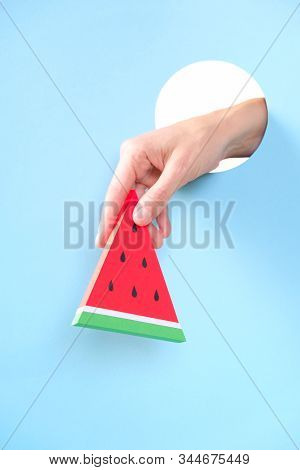 Human Hand Protruding Through Hole In Blue Background, Holding Watermelon.