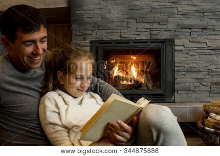 Happy Christmas family, Loving parents father and child girl sitting near fireplace and fun celebrating festive holiday enjoying feast at home