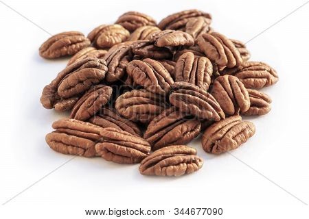 Selective Focus Close Up Of A Plie Of  Delicious Organic Shelled Pecan Nuts , On A White Background