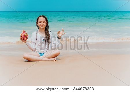 Charming Teenager Girl In A White Shirt And With Long Hair Meditates In A Lotus Position On The Seas