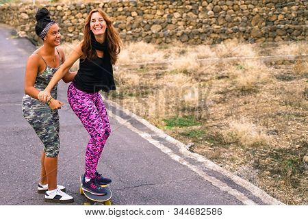 Young Mother Practising On Skateboard In The Rural Street. Daughter Helping Mum On Skateboard. Mum L